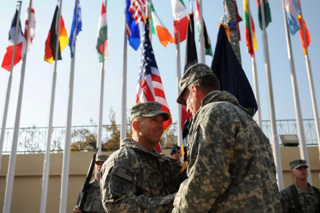 Lt. Gen. William B. Caldwell, IV, left, receives the Combined Security Transition Command - Afghanistan guidon from Gen. Stanley McChrystal, International Security Assistance Force and U.S. Forces Afghanistan commander, during the ceremony marking the change of command and the official activation of the NATO Training Mission - Afghanistan at Camp Eggers in Kabul, Nov. 21, 2009. Caldwell assumed command from Maj. Gen. Richard P. Formica, and the Combined Security Transition Command - Afghanistan merged with the new NATO Training Mission - Afghanistan to create a unified command responsible for building capability and capacity within the Afghan Ministries of Defense and Interior.