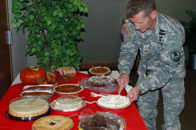 Maj. Eric Little, executive officer for the Deputy Commanding General for Operations, cuts an assortment of pies in preparation for the USASMDC/ARSTRAT Colorado Springs Thanksgiving feast.