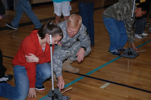 1st Space Brigade Commander Col. Jeffrey A. Farnsworth assists a student from the Galileo School of Math and Science in creating a bridge.