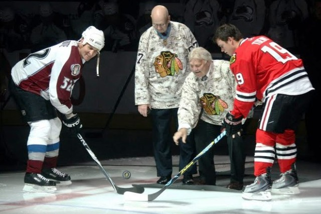 """Former Chicago Blackhawk Hockey player and a 1983 Inductee to the Hall of Fame Bobby Hull, otherwise known as """"The Golden Jet,"""" from his 23 years in the NHL, drops the puck at the 2009 Chicago Blackhawks Veterans Day game, 2009.  Hull, also a retired Canadian ice hockey player, is regarded as one of the greatest ice hockey players of all time and almost certainly, the best left-winger to ever play the game, wears a camouflage jersey for the occasion."""