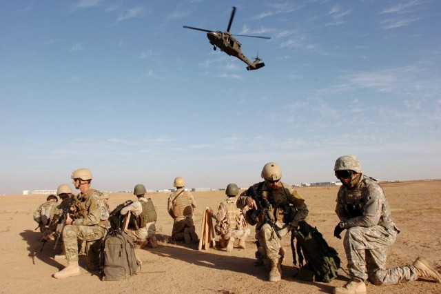 Soldiers from Company F, 425th Infantry (Airborne), Long Range Surveillance, Michigan National Guard and commandos from the 3rd Iraqi Army based in Al Kisuk, Iraq, await extraction just outside of Biyaj, Iraq, Nov. 7.