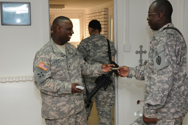 Staff Sgt. Joe Stanfield (left), brigade chaplain assistant, hands out a suicide intervention card to Staff Sgt. Leroy Williams after a suicide prevention class.
