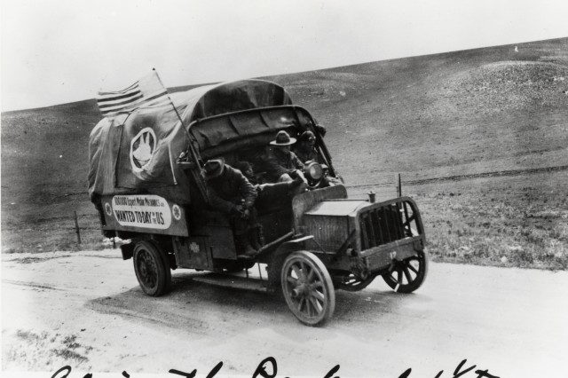 A 1 1/2-ton Packard sporting a recruiting sign heads down a dusty road during the original 1919 transcontinental motor convoy.
