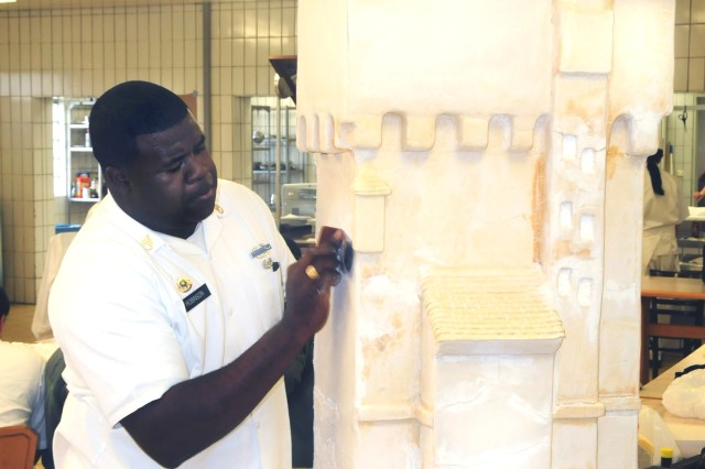 Sgt. Levy Robinson, Team Grafenwoehr, touches up a dough replica of the Grafenwoehr Water Tower in preparation for the static display portion of the U.S. Army Europe Culinary Arts Competition, Nov. 13. Robinson was one of 12 chefs who made the USAREUR team.
