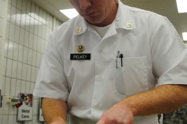 """Pfc. William Pelkey, from Team Grafenwoehr, prepares a chicken using a technique known as """"French breasting"""" during the U.S. Army Europe Culinary Arts Competition, Nov. 13."""