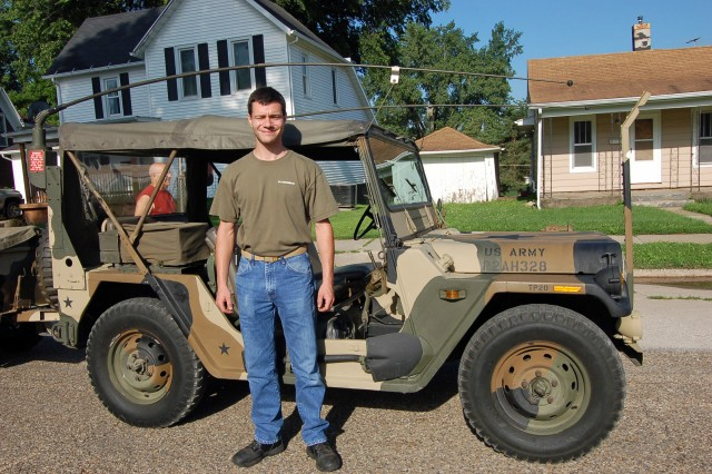 Convoy driver Joe Schaeffer poses beside a 1972 AM General M151A2, owned by Bill Barnes, during a stop in Gretna, Neb.