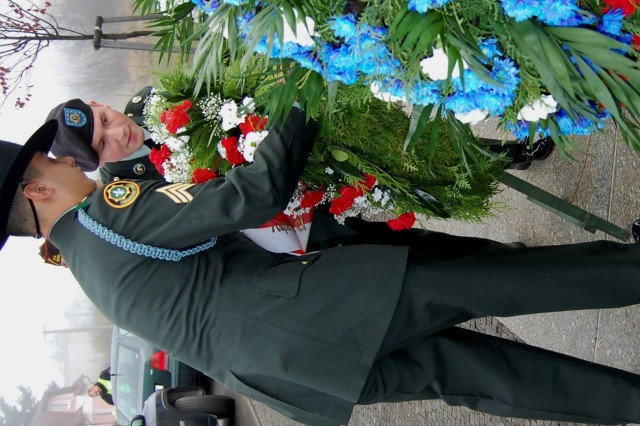 Sgt. Jesus Pulido, 2nd Stryker Cavilry Regiment, foreground, is assisted by another 2SCR Soldier in placing a wreath at the Rokycany demarcation ceremony, Nov. 14.