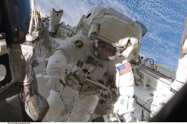 Army astronaut Col. Tim Kopra maneuvers himself within the space shuttle Endeavor's cargo bay.