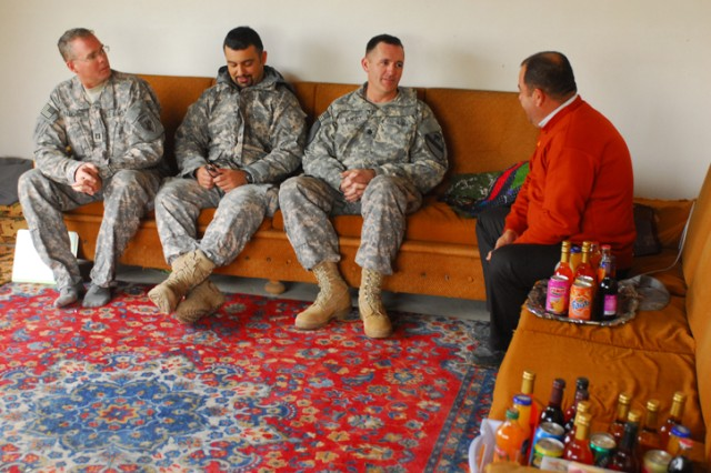 Shwan Tahir Hussein (right), speaks with Lt. Col. Hugh McNeely, the deputy commanding officer of 2nd Brigade Combat Team, 1st Cavalry Division, before receiving money for his new hoop house outside of Kirkuk, Iraq, Nov. 17. A hoop house is a place where farmers can grow crops year-round.