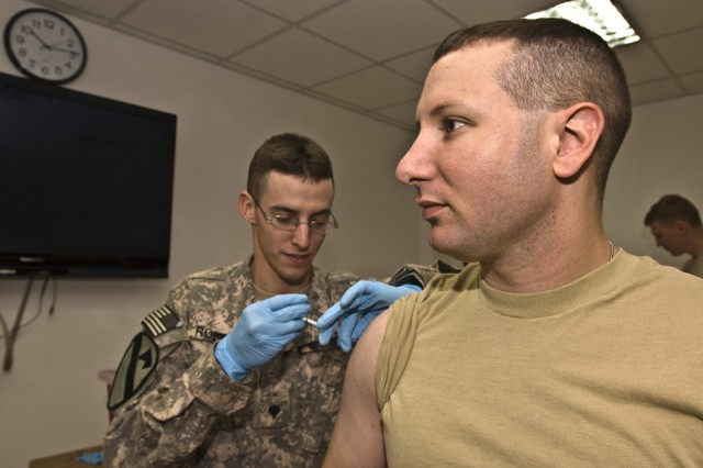 CAMP LIBERTY - Capt. Robert Magill (right), of Buffalo, N.Y., receives the H1N1 flu vaccine from Spc. Justin Roberts, here, Nov. 23. Magill is a military police officer assigned to Company A, Division Special Troops Battalion, 1st Cavalry Division. Roberts, of Galveston, Texas, is a medic assigned to the DSTB Aid Station.