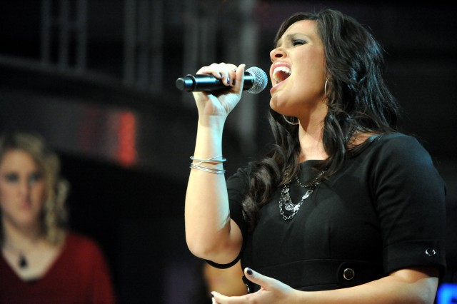 """Lisa Pratt, wife of Capt. Matt Pratt of Fort Carson, Colo., sings Aca,!A""""The ClimbAca,!A? by Miley Cyrus after being named winner of the 2009 Operation Rising Star singing contest Nov. 20, at Wallace Theater on Fort Belvoir, Va."""