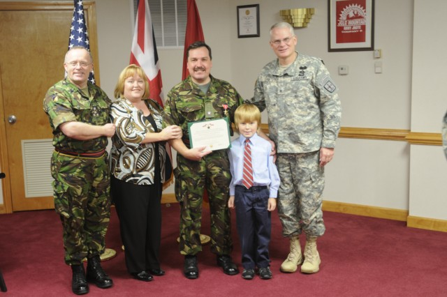 Major Dominic Gosling, (center) Royal Logistic Corps, receives the Bronze Star for his exemplary service while assigned to 7th Sustainment Brigade during OIF 07-09. Gosling is assigned to the brigades Plans and Operations section as part of the United Kingdom officer exchange program. Brigadier Gen. Brian R. Layer, (right) commanding general, chief of transportation and commandant of the U.S. Army Transportation School, presented the Bronze Star to Gosling Thursday afternoon in a ceremony held in the post headquarters commander's conference room. Attending the ceremony were Gosling's wife and son, Brigadier Chris Murray, (left) Director, Royal Logistic Corps, Col. Charles Maskell, commander, 7th Sustainment Bridgade and fellow senior leaders of the brigade and Royal Logistic Corps.
