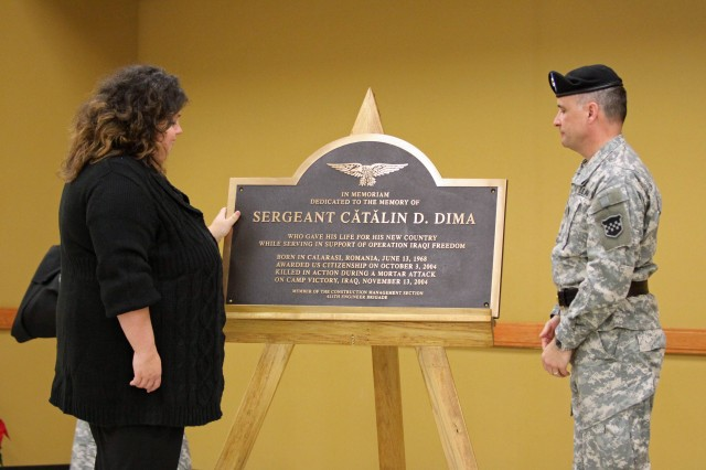 """Mrs. Florika Dima (left) looks at the memorialization dedication plaque that Maj. Gen. William Monk III, Commanding General, 99th Regional Support Command (right) unveiled at the Sgt. Catalin D. Dima Memorialization Ceremony in New Windsor, New York.   Dima, originally from Romania, served in the Romanian Navy and then came to the United States in search of the """"American Dream""""  and was granted US citizenship in October 2004.  Sadly, his dream ended on November 13, 2004, when he was promoted to the rank of sergeant and killed in action on the same day during a mortar attack at Camp Victory, Iraq. (Photo by SSG Alyn-Michael Macleod)"""
