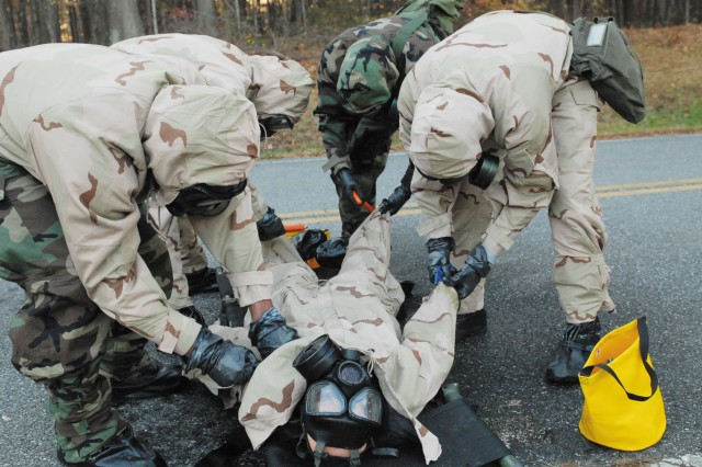 New Company A Soldiers remove a victim's contaminated clothing during a training exercise Nov. 6. The Soldiers ran two miles, stopping every quarter of a mile to test their abilities as a chemical response team and technical escort unit.