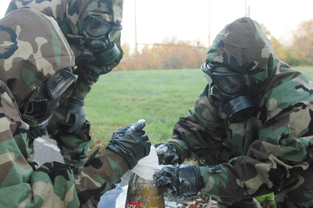 Veteran Soldiers of Company A, 22d Chemical Battalion, seal a chemical round found during the training exercise.