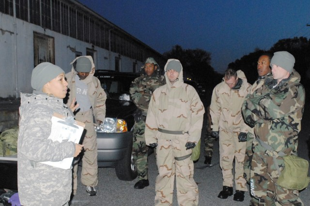"""First Lt. Maritzabel Mustafaa gives Company A, 22d Chemical Battalion Soldiers a safety briefing in the pre-dawn hours. Mustafaa organized the """"Responder's Challenge,"""" a program aimed at combining physical fitness with combat-focused"""