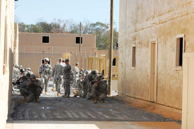 Basic training Soldiers learn how to detect and react to possible bombs at the new IED village on Sand Hill.  The training area was used for the first time Thursday after three months of construction.  The village, which was designed to mock a realistic theater situation, features a mosque and an open market.