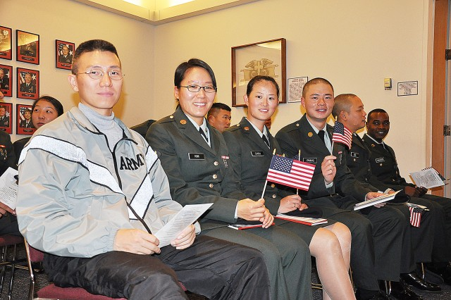 Soldiers assigned to the 232nd Medical Battalion hold U.S. flags after taking the U.S. Oath of Allegiance during a naturalization ceremony Nov. 20 at the Army Medical Department Museum auditorium.
