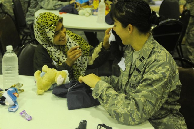 An Iraqi child shows Capt. Holly A. O'Connor, an intensive care unit nurse with the 332nd Expeditionary Medical Group and a St. Louis native, a stuffed animal at Iraqi Kid's Day Nov. 21 at Joint Base Balad, Iraq. It was the first time girls participated in the events.