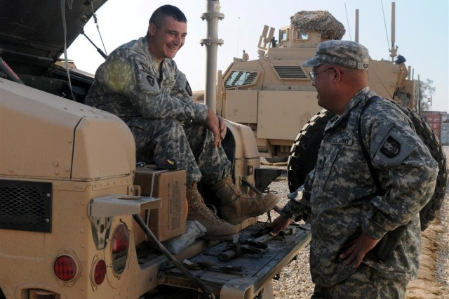 Spc. Michael P. Garton, a gunner with the Personal Security Detachment, with the 36th Sustainment Brigade out of Temple, Texas, and a Texarkana, Texas, native, relaxes on a Humvee and shares a laugh with Spc. Rolando R. Flores, a gunner with the PSD and a San Antonio native, during a break in preparations for a mission Nov. 23 in the maintenance yard at Contingency Operating Location Adder, Iraq.