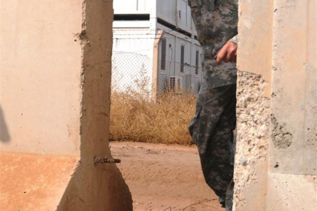 Chief Warrant Officer 4 Alan R. Hoock, a counter-improvised explosive device officer with the 90th Sustainment Brigade and a Columbia, Ill., native, sets up a mock IED for the C-IED level two training class Nov. 19 at Debro range at Joint Base Balad, Iraq.