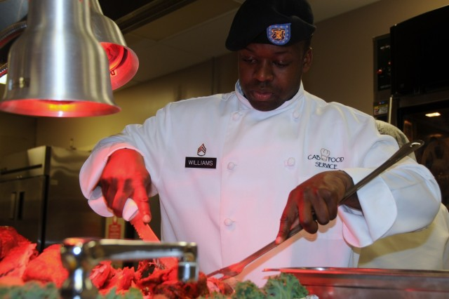 """Staff Sgt. Ahmad Williams, a Soldier and food service personnel member with the Combat Aviation Brigade's dining facility, carves a baked ham during the CAB Dining Facility's Thanksgiving dinner Nov. 25 at Fort Riley, Kan. More than 750 Soldiers and their Families attended the dinner themed """"Experience a Thanksgiving Feast of History."""""""
