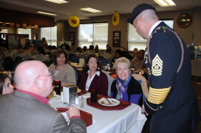 """Combat Aviation Brigade Command Sgt. Maj. James Thomson talks with Patricia Muth of Maryland, mother of CAB Commander, Col. Frank Muth, during the CAB Dining Facility's """"Thanksgiving Feast of History"""" Nov. 25 at the CAB Dining Facility, Fort Riley, Kan. More than 750 CAB Soldiers and their Families attended the early Thanksgiving celebration."""