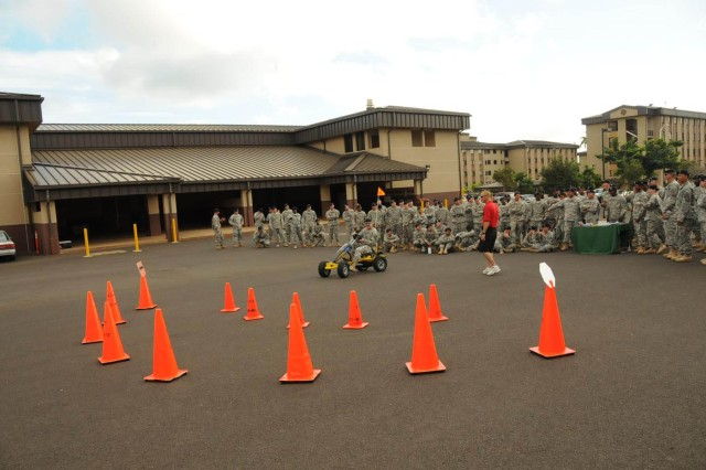 Soldiers from the 25th Transportation Company watch on as one of their own prepares to enter the drunk goggles course during the safety stand down day, Nov. 25, at Schofield Barracks.