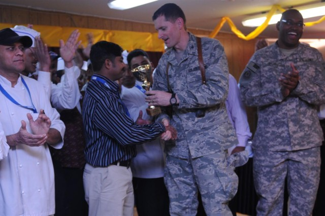 Col. David DeMartino, commander of the 332nd Expeditionary Mission Support Group, hands the first place trophy to Matthew Manoj, manager of Castle Heights, dining facility three, and a Kerala, India, native. Castle Heights won the title of best DFAC at Joint Base Balad, Iraq, after the sixth annual Thanksgiving Day competition.