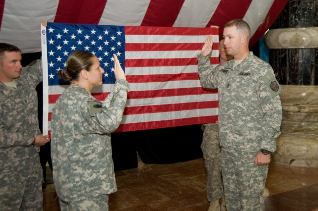 Sgt. 1st Class Darrell Sammons (right) is administered the oath of enlistment by his wife, Warrant Officer Laurimar Sammons, Nov. 25, in the rotunda of Camp Victory's Al Faw Palace in Baghdad, Iraq.