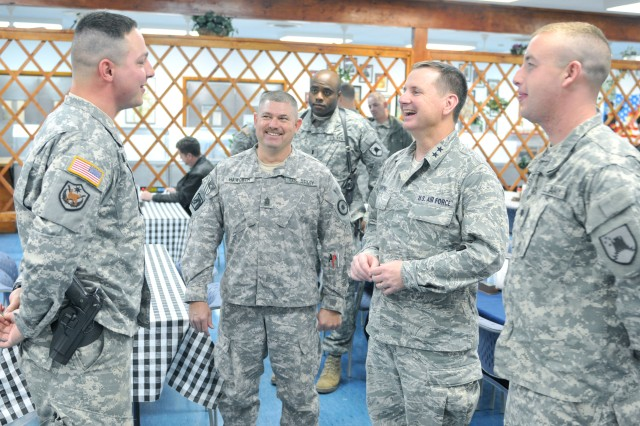 Air Force Maj. Gen. Tod M. Bunting, Kansas National Guard adjutant general, talks recently with Spc. Timothy E. Stewart, Manhattan, Kan.; and Spc. Jordan N. Meier, Shawnee, Kan.; during a dinner at Camp Bondsteel, Kosovo. Bunting was in Kosovo, visiting more than 20 Soldiers of the Kansas National Guard. Stewart and Meier were given coins by Bunting for their professionalism and positive attitudes.