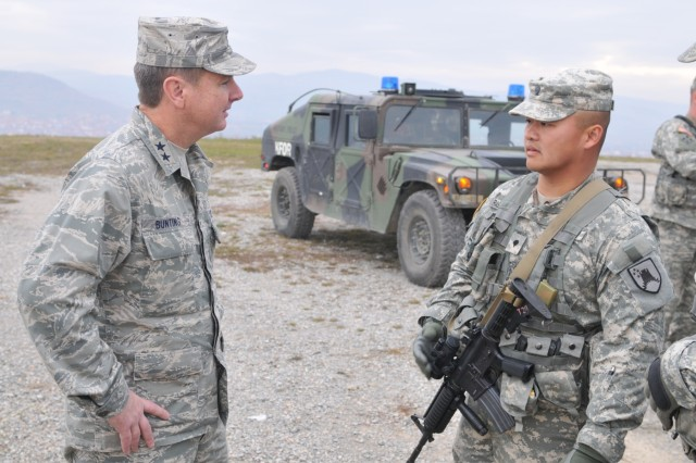 "Air Force Maj. Gen. Tod M. Bunting, Kansas National Guard adjutant general, talks with Spc. Hatsady Rasphangthong, of Excelsior Springs, Mo., during a stop at ""Memorial Hill"", an overlook of Gnjilane/Gjilan, Kosovo. Bunting recently visited more than 20 Soldiers of the Kansas National Guard who are deployed here."