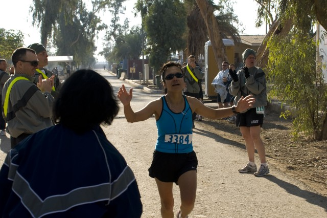 Warrant Officer Olga Elliott runs across the finish line as the first women with a time of 3 hours, 12 minutes, and 40 seconds in the Seattle Shadow Marathon Run in Baghdad, Iraq at Camp Victory on Nov. 29.