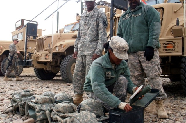 CONTINGENCY OPERATING LOCATION Q-WEST, Iraq - Spc. Marcus D. Glass (standing, left), a gunner from Magee, Miss., and Spc. Martin D. Wilson, a driver from Mendenhall, Miss., watch as Sgt. Victoria M. Moffett, a truck commander from Collins, Miss., inspects the team's personal protective equipment and escalation of force items in the company motor pool at Contingency Operating Location Q-West before a mission Nov. 21. All three belong to 1st Platoon, A Company, 106th Brigade Support Battalion out of Magee, Miss., a convoy security unit attached to 2nd Battalion, 198th Combined Arms, out of Senatobia, Miss.