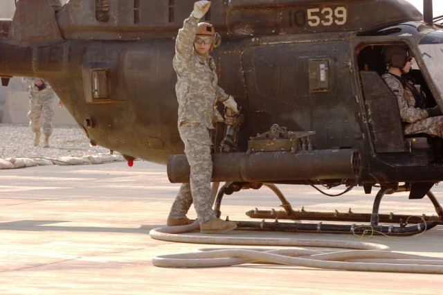 Specialist David Romano, a native of Jackson, Tenn., and qualified FARP specialist, Tennessee Army National Guard, 1-230th Air Cavalry Squadron, signals to the fuel truck operator to cut off supply as he completes the refueling of an OH-58D Kiowa Warrior, Nov. 11. (Photo by Staff Sgt. Mike Alberts, 25th Combat Aviation Brigade, 25th Infantry Division Public Affairs)