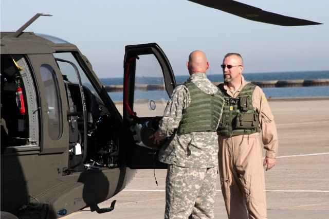 Crew members Chief Warrant Officer Kevin Calloway and Sgt. 1st Class Jesus Colon discuss preflight and briefing requirements prior to climbing aboard the last UH-60 A-to-A recapitalized helicopter to leave Corpus Christi Army Depot in Texas.