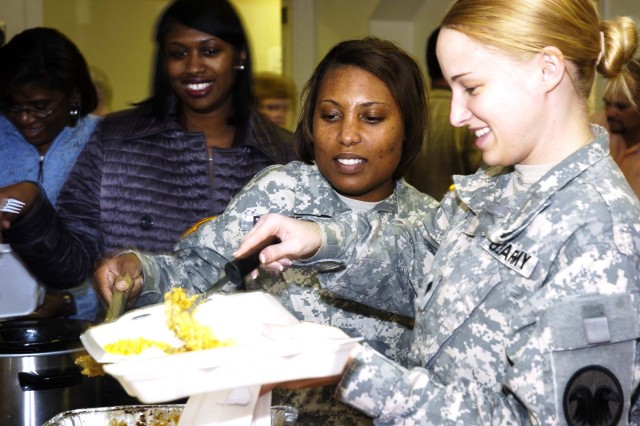 Spc. Michelle Hard (right) and Staff Sgt. Demetria Palmer (center), administrative NCOs with Company C, U.S. Army Reserve Command, load up on food.