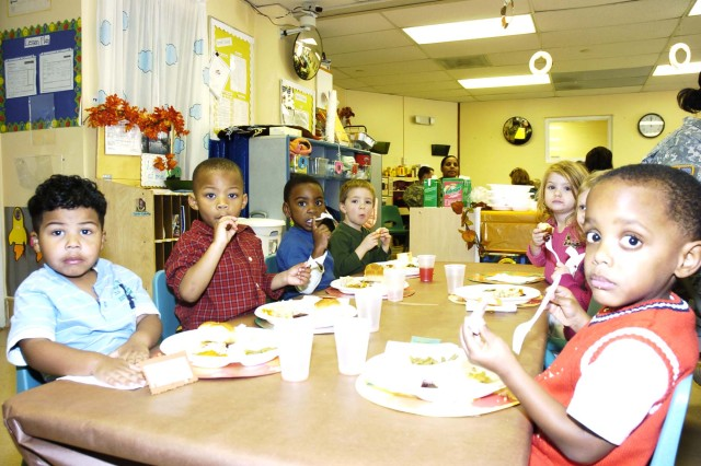 Children in the Fort McPherson Child Care Center Preschool 3 class enjoy a meal in their classroom as a pre-Thanksgiving celebration. The children's parents were invited to dine with them and enjoy food, such as turkey, ham, rice, stuffing, green beans, sweet potatos and fresh rolls. Desserts, which included apple and pumpkin pies, were also offered. After their bellies were full, the students showed off their homemade turkey costumes and put on a Thanksgiving Day skit for their parents