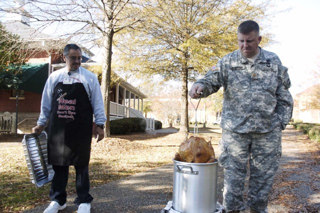 Maj. Doug McBride, an operation officer with U.S. Army Forces Command G-1, pulls a turkey from a fryer outside the chapel center to prepare for a lunch later in the day.