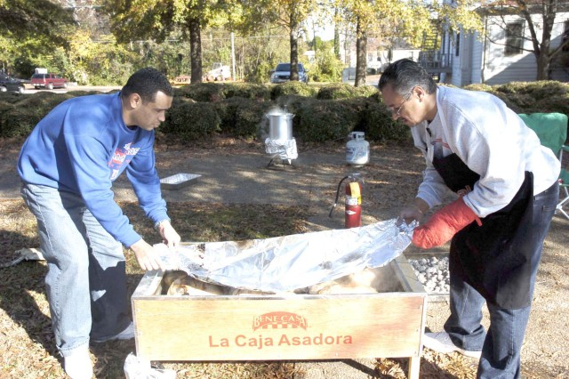 Maj. Hector Roman (left), an operation officer with FORSCOM G-1, and Luis Feliciano (right), chief of operations branch for FORSCOM G-1, remove the cover of a smoke box containing several turkeys for a FORSCOM luncheon. The two also smoked hams and fried turkeys.