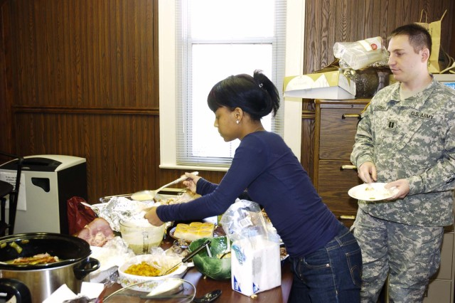At right: Members of the U.S. Army Garrison Office of the Staff Judge Advocate Group office enjoy their own pre-Thanksgiving luncheon. Courtney Parker, 19, daughter of Marcia Parker, chief of client services, grabs some food while Capt. Craig Silverman (right), chief of military justice, waits his turn.