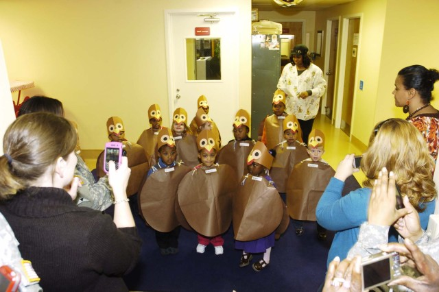 Children from the Preschool 3 Class at the Fort McPherson Child Care Center get ready to perform a skit for their parents, who wait to capture the action on their cameras. Parents came by the center to have a Thanksgiving dinner with their children Nov. 20 and received the added bonus of seeing them perform in their homemade turkey costumes.
