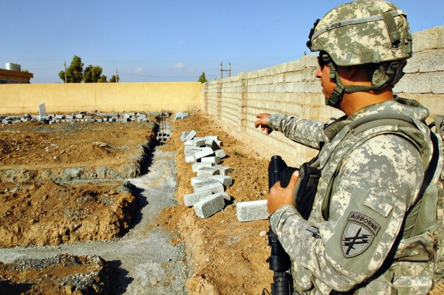 Sergeant First Class Raymond Loriaux, from San Antonio with U.S. Army Civil Affairs Battalion, surveys the foundation of a new secondary school being built in Kalour village in Kirkuk province, Iraq, Nov. 22.