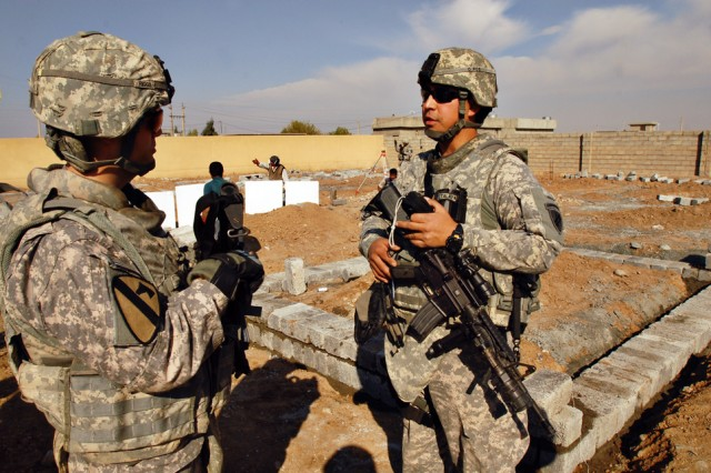 First Lieutenant Bryan Riggs (left), from Stanton, Ky., and a platoon leader in 1st Battalion, 8th Cavalry Regiment, 2nd Brigade Combat Team, 1st Cavalry Division, and Sgt. 1st Class Raymond Loriaux (right), from San Antonio with U.S. Army Civil Affairs Battalion, survey the foundation of a new secondary school being built in Kalour village in Kirkuk province, Iraq, Nov. 22.