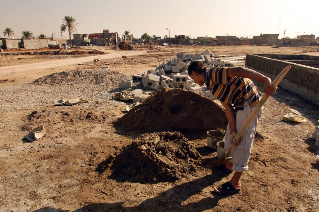A Taza, Iraq, resident loads cement with a shovel to help a neighbor rebuild his home, one bucket at a time, following a devastating car-bomb attack which killed approximately 90 residents and wounded more than 200 in Taza last June. Reconstruction in the area has seen progress.