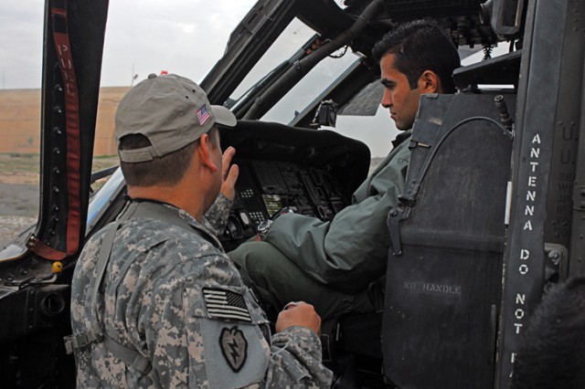 Chief Warrant Officer Steve Bridges, a Hilo, Hawaii, native and the standardization instructor pilot for 2nd Squadron, 6th Cavalry Regiment, Aviation Brigade of the 25th Infantry Division, shows 2nd Lt. Karam Ebrahem, an Iraqi Air Force student training to become a helicopter pilot, the inner workings of a helicopter during an open house at Forward Operating Base Warrior, Kirkuk, Iraq, Nov. 25. The 2nd Sqdn. 9th Cav. Regt. invited the group of IAF pilots to visit their working area and show them around.