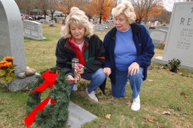 Jennifer Hames and Joy Parker read words of remembrance attached to a holiday wreath placed on a veteran gravesite at Maple Hill Cemetery. They are leading efforts by the Redstone Garden Club to decorate veteran gravesites in Madison County with holiday wreaths.
