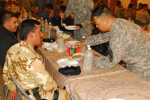 Capt. Eric Hong, the commander of Company B, 1st Battalion, 8th Cavalry Regiment, 2nd Brigade Combat Team, 1st Cavalry Division, ladles gravy onto mashed potatoes for one of his Iraqi partners during a Thanksgiving meal at Joint Security Station McHenry in Kirkuk province, Iraq, Nov. 24. The meal was hosted by 1st Bn., 8th Cav. Regt., and was an opportunity to share a traditional U.S. holiday with them.