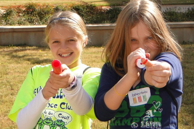 Maggie Holsclaw, left, of Priceville Elementary School and Sydney Parris of Central School take aim with their rockets during some free flowing fun time outside the Shelby Center at the University of Alabama-Huntsville during Girls' Science and Engineering Day.