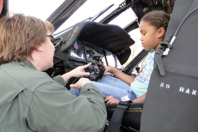 Lisa Thompson, a flight test engineer with the Redstone Test Center, explains the controls of a Black Hawk helicopter to Kayla Clark. The Black Hawk landed on the front lawn of the Shelby Center for Science and Engineering at the University of Alabama-Huntsville as a special treat for the 454 girls who attended the Girls\' Science and Engineering Day.